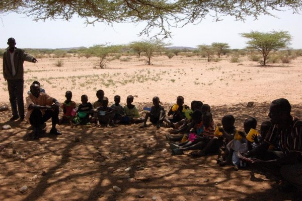 Children sitting on the ground at Dubsahaay, Rendille at meal time